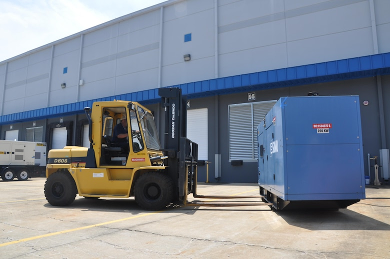 A member of the Federal Emergency Management Agency's Emergency Support Function transports a generator during an interagency regional power mission exercise held at the FEMA Distribution Center in Atlanta, Georgia July 20. The team replicated a temporary emergency power deployment in response to a simulated natural disaster. The three-day training and exercise tested the unit's ability to execute temporary emergency power operations.
