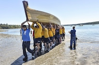 Sailors assist in transporting a tribal canoe, some weighing more than 1,500 pounds, during a canoe landing the Port Gamble S'Klallam Tribe hosted in Kingston, Wash., July 24, 2016. The sailors are assigned to Naval Base Kitsap. During the event, Pacific Northwest tribes traveled via canoe to tribal sites, culminating in a landing in Olympia, Wash. Navy photo by Petty Officer 2nd Class Cory Asato