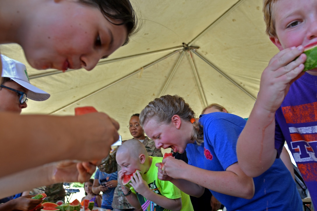 Team Shaw children participate in a watermelon eating contest during the Exceptional Family Member Program Kid's Jamboree at Shaw Air Force Base, S.C., July 27, 2016. Parents and children had the opportunity to participate in bounce house activities, various informational booths and standard health screenings. (U.S. Air Force photo by Airman 1st Class Christopher Maldonado)