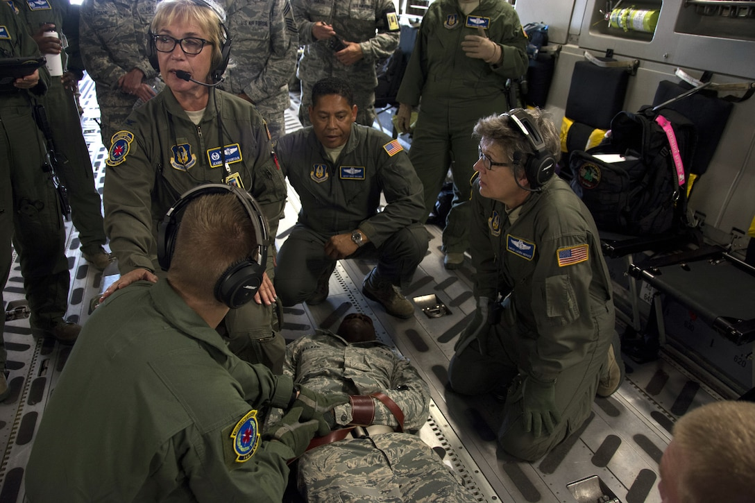 Col. Jeanne LaFountain, 349th Aeromedical Evacuation Squadron commander, instructs Airmen how to properly detain an aggressive passenger aboard a C-17 Globemaster III, during Exercise Patriot Wyvern, July 23,2016. The 349th Aeromedical Staging Squadron, 349th Medical Squadron and the 349th Aeromedical Evacuation Squadron practiced in-flight emergency and evacuation processes during the training event at Travis Air Force base, Calif. Patriot Wyvern is a hands-on, bi-annual event conducted by the 349th AMW, and designed to hone combat skills and improve organizational interoperability. (U.S. Air Force photo by Senior Airman Sajjan Singh)