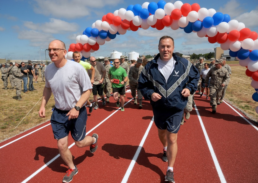 Oregon Air National Guard Col. Paul Fitzgerald, 142nd Fighter Wing commander, left, and Chief Master Sgt. Chris Roper, 142nd Fighter Wing command chief, right, lead a group of Airmen and base staff during a ceremonial first lap as part of the official opening of the new base track, Portland Air National Guard Base, Ore., July 26, 2016. (U.S. Air National Guard photo by Tech. Sgt. John Hughel, 142nd Fighter Wing Public Affairs/Released)