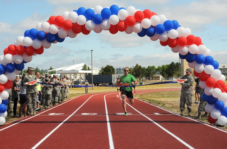 Oregon Air National Guard Staff Sgt. Alan Plank, assigned to the 142nd Fighter Wing Maintenance Group, crosses the finishing line and cuts the ceremony opening ribbon during the inaugural first race on the new track at the Portland Air National Guard Base, Ore., July 26, 2016. (U.S. Air National Guard photo by Tech. Sgt. John Hughel, 142nd Fighter Wing Public Affairs/Released)