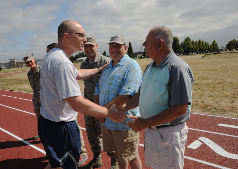 Oregon Air National Guard Col. Paul Fitzgerald, 142nd Fighter Wing commander, left, thanks Mike Godsey, right, during the official opening of the new base track as he acknowledges members from the 142nd Fighter Wing Civil Engineer Squadron who helped build the newest on base construction project, July 26, 2016, Portland Air National Guard Base, Ore. (U.S. Air National Guard photo by Tech. Sgt. John Hughel, 142nd Fighter Wing Public Affairs/Released)