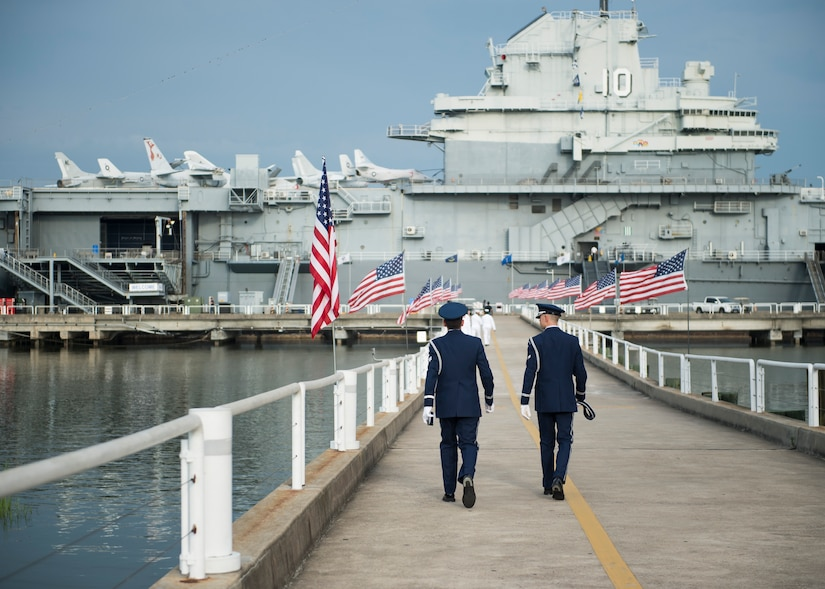 Airmen walk towards the USS Yorktown before the Naval Support Activity Charleston change of command, July 21, 2016, Charleston, S.C. U.S. Navy Capt. Robert Hudson took command of NSA Charleston from his predecessor Capt. Timothy Sparks. Hudson previously served as the Nuclear Power Training Unit Charleston commander. Sparks is retiring after 38 years of military service. (U.S. Air Force photo/Staff Sgt. Jared Trimarchi)