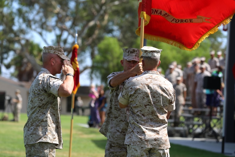 Lt. Gen. David H. Berger, the outgoing commanding general of I Marine Expeditionary Force, passes the unit colors to Lt. Gen. Lewis A. Craparotta during a change of command ceremony at Camp Pendleton July 27, 2016. Berger is set to become the next U. S. Marine Forces Pacific commander in August of 2016.  (U.S. Marine Corps photo by Cpl. Garrett White/ RELEASED)