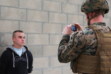 U.S. Marine Corps Sgt. Taylor R. Lefevre, with Special Purpose Marine Air-Ground Task Force-Crisis Response-Africa captures a photo of a simulated civilian for future identification during a Non-combatant evacuation operation exercise hosted by French Army Center for Urban Combat Training instructors aboard Camp Sissonne, France, June 21, 2016. SPMAGTF-CR-AF Marines trained alongside a company of French Army soldiers, integrating their skills and resources to form an effective battle plan, similar to what they may face in the event of a future crisis. (U.S. Marine Corps photo by Sgt. Kassie L. McDole/Released)