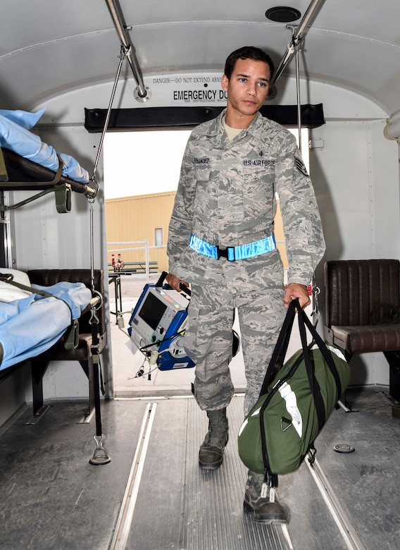 Staff Sgt. Luis Hernandez, a medical technician with the 379th Enroute Patient Staging Facility, carries an Zoll monitor/defibrillator used to monitor the cardiovascular status of a patient and for emergency management of a cardiac dysrythmia and a bag with airway and breathing supplies on July 18, 2016 at Al Udeid Air Base, Qatar. Hernandez and the staff of the EPSF prepared a bus to carry 14 patients and a military working dog and his handler transitting through the area of responsibility on their way to advanced care in Germany.  (U.S.Air Force photo/Technical Sgt. Carlos J. Trevino/Released)