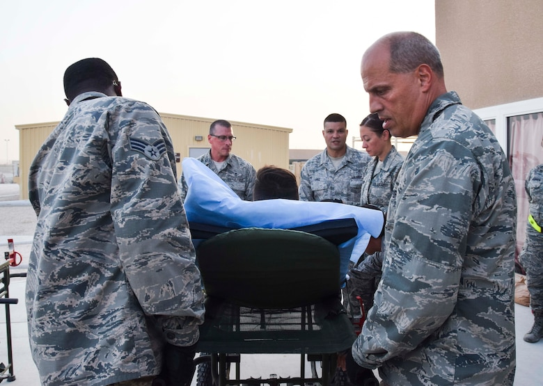 Lt. Col. Chris Hull (right), flight commander of the 379th Enroute Patient Staging Facility, leads his medical team during the loading of a stretchered patient onto an ambulance for evacuation July 18, 2016 from Al Udeid Air Base, Qatar.  The team moved 14 patients, including a military working dog, onto a C-17 Globemaster III flight to U.S. military facilities in Germany. (U.S. Air Force photo/Technical Sgt. Carlos J. Treviño)
