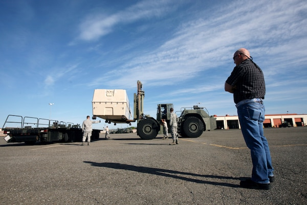 "John ""Buck"" Buchanan, front right, watches as members of the 60th Aerial Port Squadron use a forklift to load a piece of cargo at Travis Air Force Base. DLA's Warfighter Support Representatives visited Buchanan and the 60th APS as part of WSR training at DLA Distribution San Joaquin, Calif."