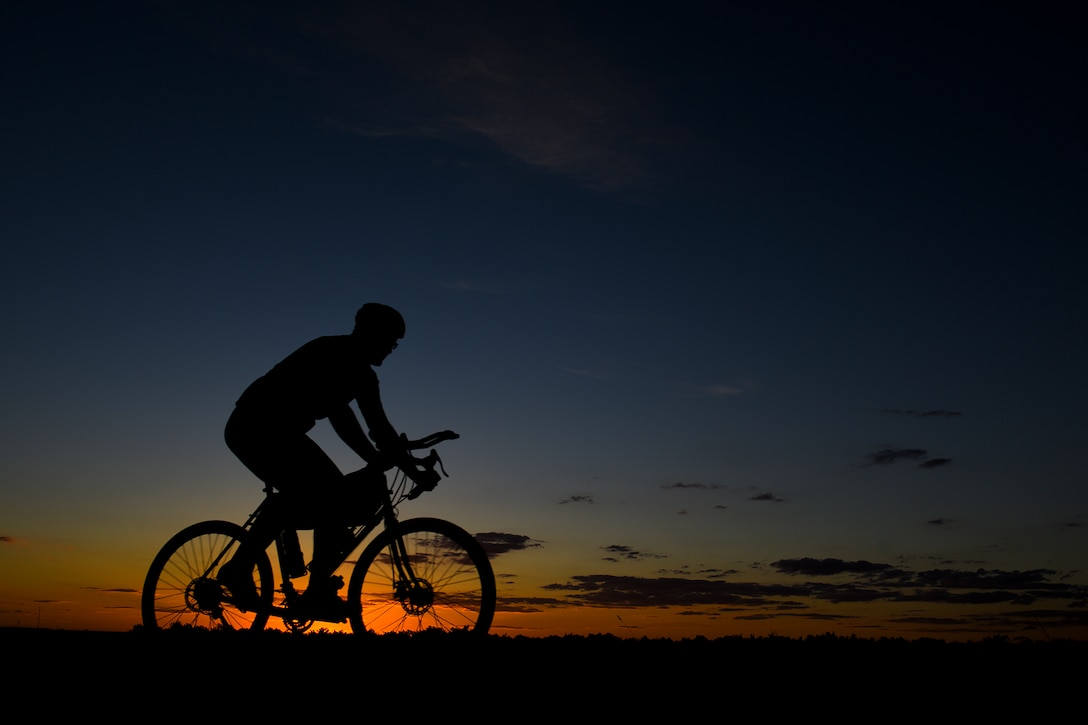 The sun sets on the horizon as Staff Sgt. Kyle Emmel, a 17th Training Group student, cycles down a road in San Angelo, Texas, July 19, 2016. When he rides, Emmel said his mind goes blank and all that exists in that moment is him, his bike and the landscape around him. (U.S. Air Force photo/Senior Airman Devin Boyer)