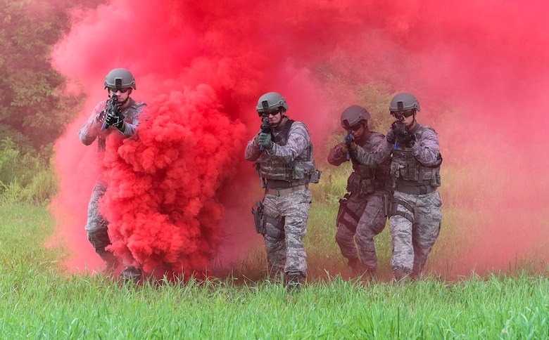 Airmen with the 182nd Security Forces Squadron, Illinois Air National Guard, maneuver through concealment smoke during shoot, move, communicate training in Peoria, Ill., July 20, 2016. The training was designed to practice fire team communication and movements while engaging simulated combatants. (U.S. Air National Guard photo/Staff Sgt. Lealan Buehrer)