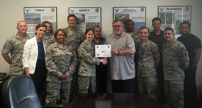 "James Brown, front right, 47th Flying Training installation deployment officer, accepts the ""XLer of the Week"" award from Col. Michelle Pryor, front left, 47th Flying Training Wing commander, here, July 20, 2016. The XLer is a weekly award chosen by wing leadership and is presented to those who consistently make outstanding contributions to their unit and Laughlin. (Courtesy photo)"