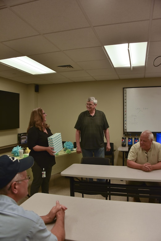 George Kelly, vehicle maintenance manager, receives his retirement gift from Carrie Gernhardt, project manager for Maytag Aircraft Corporation, at the Pittsburgh International Air Reserve Station, Pennsylvania, July 26, 2016. Kelly is retiring after 37 years at the 911th Airlift Wing. (U.S. Air Force courtesy photo by Ashley Podrasky)