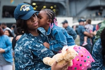 Navy Petty Officer 1st Class Donisha Brown reunites with her daughter during a homecoming celebration for the aircraft carrier USS Ronald Reagan at Commander, Fleet Activities Yokosuka, Japan, July 26, 2016. The Ronald Reagan Carrier Strike Group conducted 53 days of strike group operations to improve combat readiness, develop cohesion as a strike group and engage its partners in the region. Navy photo by Petty Officer 3rd Class James Lee