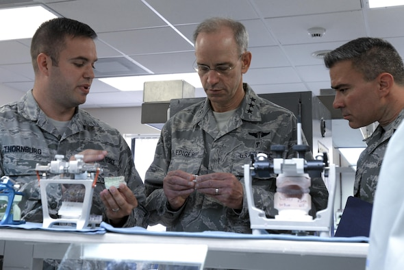 U.S. Air Force Lt. Gen. Mark A. Ediger, middle, Surgeon General of the Air Force, and Chief Master Sgt. Jason E. Pace, right, Chief, Medical Enlisted Force, examine dental equipment at the 48th Dental Squadron dental lab at Royal Air Force Lakenheath, England, July 25. Ediger and Pace visited many of the 48th Medical Group's facilities during their tour to engage with Airmen and see first-hand the capabilities of Liberty medics. (U.S. Air Force Photo by Airman Eli Chevalier)