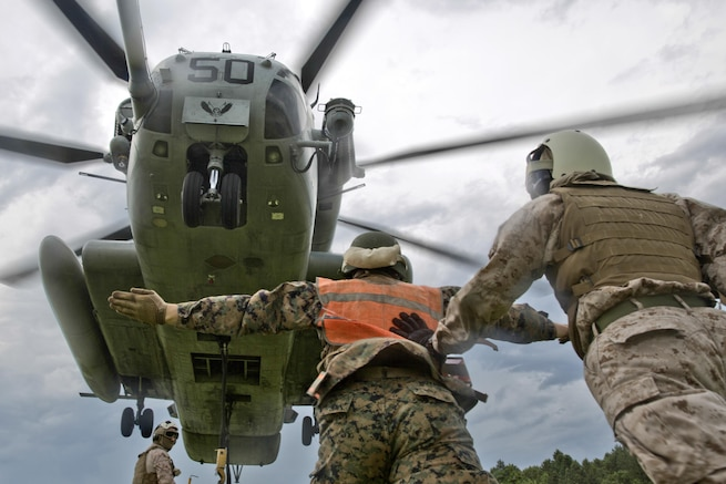 A Marine uses hand and arm signals to direct a CH-53E Super Stallion during a support team exercise at Camp Lejeune, N.C., July 19, 2016. Students attended the exercise as part of their required entry-level training. Marine Corps photo by Lance Cpl. Manuel A. Serrano
