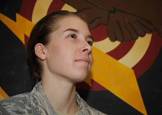 Airman 1st Class Rachel Jones from the 81st Range Control Squadron stands for a photo in front of the 81st's squadron patch at Tyndall Air Force Base, Fla., July 27, 2016. Jones was selected by her leadership as an outstanding performer. (U.S. Air Force photo by Senior Airman Solomon Cook/Released)