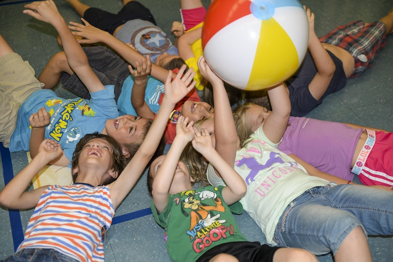 A group of children attending the base chapel's vacation bible school toss a ball over their heads in an effort to keep it from hitting the ground as part of a game at Holloman Air Force Base, N.M., on July 19. Children attending the VBS program participate in a variety of activities, ranging from science experiments to arts and crafts. (U.S. Air Force photo by Amn Alexis P. Docherty/released)
