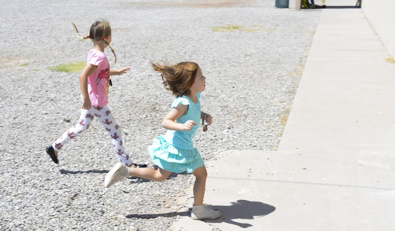 Kendall and Ava, two children attending the base chapel's vacation bible school, race to their next station after participating in an outdoor activity at Holloman Air Force Base, N.M., on July 20. Stations are set up in various rooms of the base middle school and each station hosts a different activity. (Last names are being withheld due to operational requirements. U.S. Air Force photo by Amn Alexis P. Docherty/released)