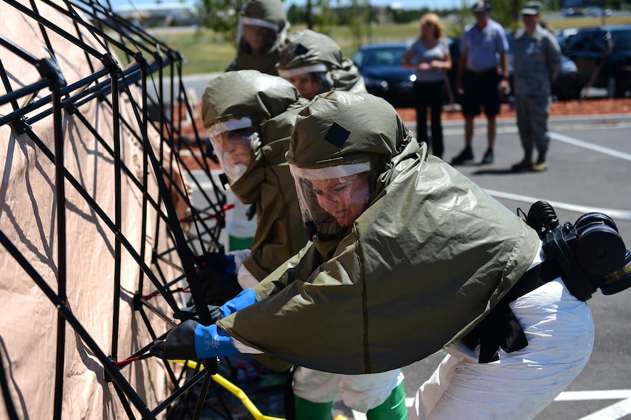 Members of the 460th Medical Group in-place patient decontamination triage and manpower/security team secure a decontamination tent July 21, 2016, during a simulated exercise on Buckley Air Force Base, Colo. The exercise had many learning points for the team, including identification of contaminants, equipment set-up and a detailed understanding of the whole decontamination process. (U.S. Air Force photo by Airman 1st Class Gabrielle Spradling/Released)