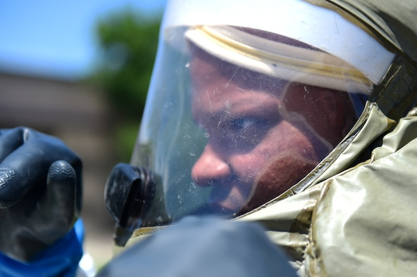 A member of the 460th Medical Group in-place patient decontamination triage and manpower/security team waits as another team member fixes part of his decontamination suit July 21, 2016, during a simulated exercise on Buckley Air Force Base, Colo. The 19-person IPPD team performed a final timed exercise, where the goal was to decontaminate mock casualties from a simulated terrorist attack using a weapon of mass destruction. (U.S. Air Force photo by Airman 1st Class Gabrielle Spradling/Released)