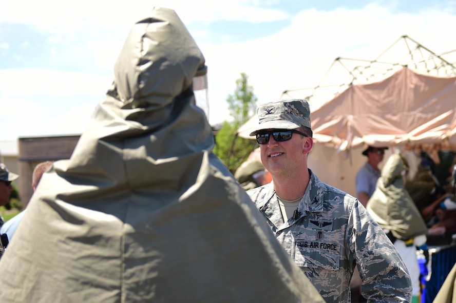 Col. Matthew Hanson, 460th Medical Group commander, speaks with a member of the 460th Medical Group in-place patient decontamination triage and manpower/security team July 21, 2016, during a simulated exercise on Buckley Air Force Base, Colo. The exercise provided the IPPD team to respond to a simulated event and be tested on their skill and know-how to decontaminate patients. (U.S. Air Force photo by Airman 1st Class Gabrielle Spradling/Released)