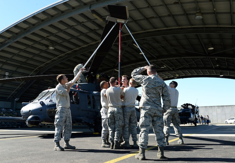 Members of the 129th Rescue Wing maintenance squadron unfold the main blades of an HH-60 Pavehawk shortly after its arrival at Royal Australian Air Force base Townsville for operation Angel Reign, June 28, 2016. The 129th MXS unfolded a total of two helicopters which were later used for multiple exercise missions alongside pararescuemen.   (U.S. Air National Guard photo by Senior Airman Zachiah Roberson/released)