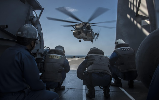 Members of the Japan Maritime Self-Defense Force prepare to receive an MH-53E Sea Dragon aboard the JS Uraga, while taking part in Mine Countermeasures Exercise 2JA in Mutsu Bay, Japan, July 22, 2016. The 99-foot-long helicopter has two missions: airborne mine counter measure and navy vertical onboard delivery. During the exercise, the U.S. Navy operated out of Misawa Air Base, Japan, to practice these missions while improving interoperability with the JMSDF. (U.S. Air Force photo by Senior Airman Jordyn Fetter)