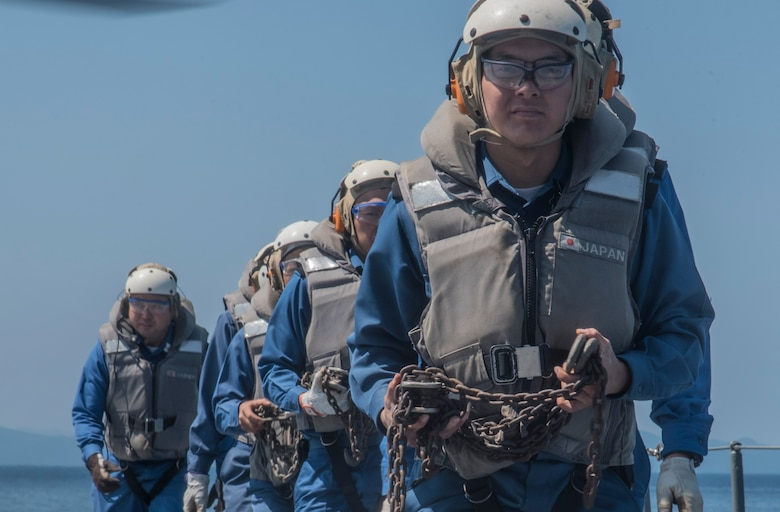 Members of the Japan Maritime Self-Defense Force walk along the helicopter landing pad of the JS Uraga while taking part in Mine Countermeasures Exercise 2JA in Mutsu Bay, Japan, July 22, 2016. While the U.S. Navy trained on boat landings, the JMSDF crew focused on receiving and securing aircraft on their vessel. If an actual mine threat were to arise, the two services could work together to eliminate it using resources like explosive ordnance disposal units, minesweeper ships and mine countermeasure helicopters. (U.S. Air Force photo by Senior Airman Jordyn Fetter)