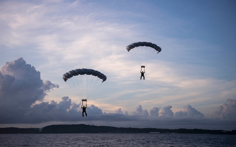 Two pararescuemen, from Kadena Air Base's 31st Rescue Squadron, parachute into the Pacific Ocean during a rescue training scenario June 29, 2016. Pararescuemen train both night and day to maintain critical skills for their missions. (U.S. Air Force photo by Senior Airman Omari Bernard)