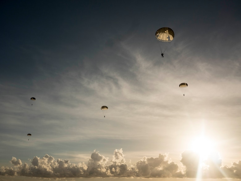 U.S. Air Force pararescumen, from the 31st rescue squadron, Kadena Air Base, Japan, float through the air after performing a static line jump from an MC-130J Commando, June 29, 2016, over the Pacific Ocean. Pararescuemen depend on the parachutes packed by expert air crew flight equipment personnel to be able to deploy anywhere to accomplish their mission. (U.S. Air Force photo by Senior Airman Omari Bernard)
