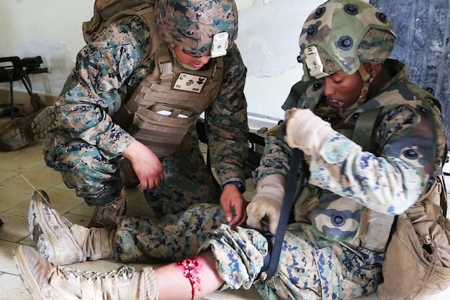 U.S. Navy hospitalman 2nd Class Jonathan Rivas, (left), with Charlie Company, 1st Battalion 8th Marine Regiment, Special Purpose Marine Air-Ground Task Force-Crisis Response-Africa assess a simulated wound on U.S. Marine Corps Lance Cpl Zachary C. Hill, (right), a team leader, during a combined arms attack aboard Camp Sissonne, France, June 21, 2016. CENZUB provided SPMAGTF-CR-AF Marines with the ability to maintain their proficiencies in urban combat and integrate with French personnel and assets in a realistic scenario. (U.S. Marine Corps photo by Sgt. Kassie McDole/Released.)