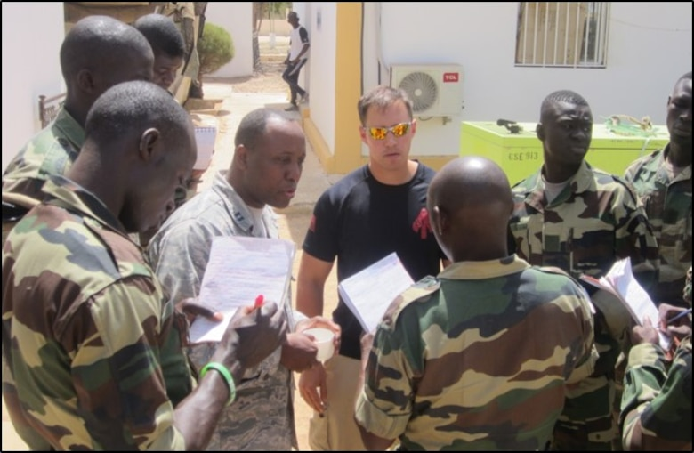 Air Force Capt. Patrick Mudimbi (left center) translates for Marine Corps Chief Warrant Officer Jonathan Ross in Senegal as they train Senegalese soldiers how to interrogate a potential informant or source.