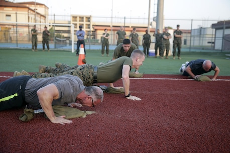 Celebrity Chef Robert Irvine and Marines with Special Purpose Marine Air-Ground Task Force Crisis Response-Africa conduct push-ups during a physical training event at Naval Air Station Sigonella, Italy, July 28, 2016.  Marines completed a circuit course with Irvine, which included upper and lower body workouts, Marine Corps Martial Arts Program techniques and laps around the baseball field.  (U.S. Marine Corps photo by Cpl. Alexander Mitchell/released)