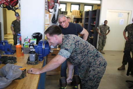 Lance Cpl. Kyle Lukoskie, a mechanic with Special Purpose Marine Air-Ground Task Force Crisis Response-Africa does some bent over curls with Celebrity Chef Robert Irvine at Naval Air Station Sigonella, Italy, July 28, 2016.  Marines displayed some of their capabilities and vehicles for Irvine and had a chance to have conversations with him. (U.S. Marine Corps photo by Cpl. Alexander Mitchell/released)