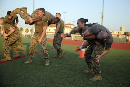Sgt. Janelle Lopez, an intelligence specialist with Special Purpose Marine Air-Ground Task Force Crisis Response-Africa, conducts a buddy squat with Celebrity Chef Robert Irvine during a physical training event at Naval Air Station Sigonella, Italy, July 28, 2016.  Marines completed a circuit course with Irvine, which included upper and lower body workouts, Marine Corps Martial Arts Program techniques and laps around the baseball field.  (U.S. Marine Corps photo by Cpl. Alexander Mitchell/released)