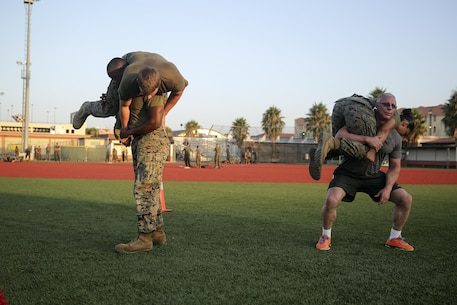 Celebrity Chef Robert Irvine and Marines with Special Purpose Marine Air-Ground Task Force Crisis Response-Africa conduct buddy squats during a physical training event at Naval Air Station Sigonella, Italy, July 28, 2016.  Marines completed a circuit course with Irvine, which included upper and lower body workouts, Marine Corps Martial Arts Program techniques and laps around the baseball field.  (U.S. Marine Corps photo by Cpl. Alexander Mitchell/released)
