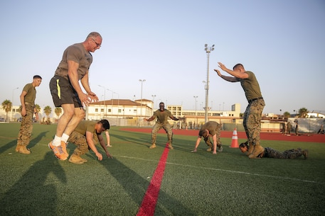 Celebrity Chef Robert Irvine and Marines with Special Purpose Marine Air-Ground Task Force Crisis Response-Africa conduct burpees during a physical training event at Naval Air Station Sigonella, Italy, July 28, 2016.  Marines completed a circuit course with Irvine, which included upper and lower body workouts, Marine Corps Martial Arts Program techniques and laps around the baseball field.  (U.S. Marine Corps photo by Cpl. Alexander Mitchell/released)
