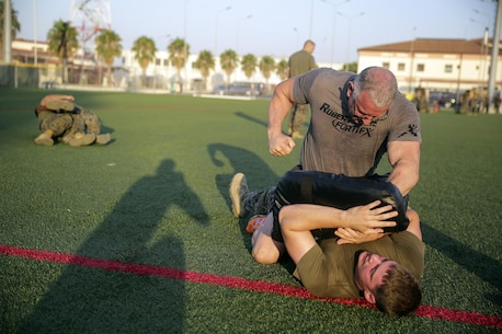 Celebrity Chef Robert Irvine and Cpl. Matthew Heldt, a ground radio repair technician with Special Purpose Marine Air-Ground Task Force Crisis Response-Africa, conduct Marine Corps Martial Arts Program techniques during a physical training event at Naval Air Station Sigonella, Italy, July 28, 2016.  Marines completed a circuit course with Irvine, which included upper and lower body workouts, MCMAP techniques and laps around the baseball field.  (U.S. Marine Corps photo by Cpl. Alexander Mitchell/released)