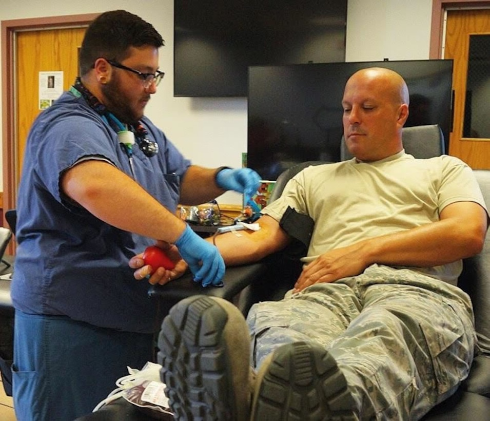 Phlebotomist Jay Cannata of Kenmore, N.Y. checks on Master Sgt. Doug Kalota, crew chief, 914 Aircraft Maintenance Group as he donates blood on Tuesday, July 19, 2016, at Niagara Falls Air Reserve Station, Niagara Falls, N.Y. With more than 20 donors, this was the most successful blood drive on base this year. (U.S. Air Force photo by Staff Sgt. Richard Mekkri/released)