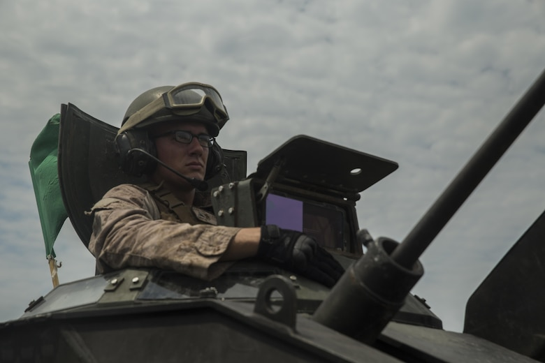 Lance Cpl. Kevin Christ, a crewman with Alpha Company, 2nd Assault Amphibian Battalion, spots targets downrange during a live-fire gunnery range at Camp Lejeune, N.C., July 27, 2016. With a max possible score of 1,000, Marines must fire through ten separate engagements compiling a score of 700 to pass.