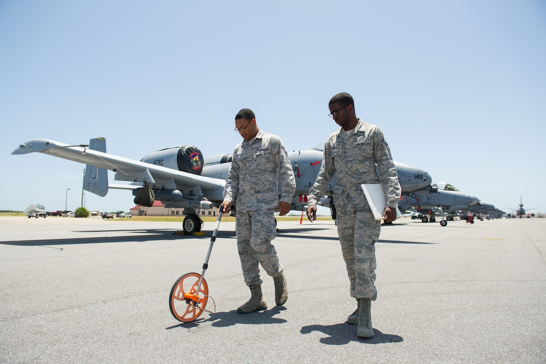Senior Airmen Damon Sheperd, airfield management operations supervisor, and Henson Greene, airfield management shift lead, measure distances between aircraft to ensure there is adequate wingtip clearance at Patrick Air Force Base, Fla., July 28, 2016. The Airmen are members of the 45th Operations Support Squadron who ensure the airfield is safe for all flying operations with routine checks of the flightline area, which includes verifying adequate wing tip clearance that prevents aircraft from being too close to each other or equipment parked nearby.   During the month of July they helped the 45th Space Wing host visiting A-10 Thunderbolt IIs from 924th Fighter Group, stationed at Davis-Monthan Air Force Base, Arizona, who were here to train with the 920th Rescue Wing's helicopter squadron, the 301st Rescue Squadron, July 18 to 29, 2016. (U.S. Air Force photos/Benjamin Thacker)
