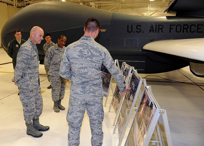 Gen. Carlton D. Everhart II, Air Mobility Command commander, left, and Chief Master Sgt. Shelina Frey, Air Mobility Command command chief, middle, listen to a briefing by Airman 1st Class Austin King, 69th Maintenance Squadron RQ-4B crew chief, July 28, 2016, on Grand Forks Air Force Base, N.D.  Everhart visited 69th Reconnaissance Group to learn about their mission during his tour of Grand Forks AFB. (U.S. Air Force photo by Senior Airman Ryan Sparks/Released)