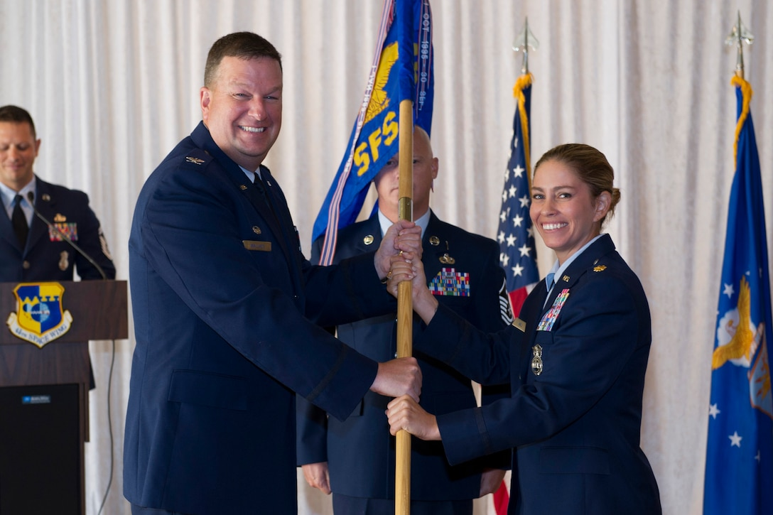Col. Matthew Wallace, 45th Mission Support Group commander, presents Maj. Megan Hall, 45th Security Forces Squadron guidon during a change of command ceremony July 29, 2016, at Patrick Air Force Base, Fla. Changes of command are a military tradition representing the transfer of responsibilities from the presiding official to the upcoming official. (U.S. Air Force photo/Matthew Jurgens)