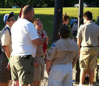 Boy Scouts Troop 149 Scoutmaster Dave Robinson discusses how to properly raise the flags June 30, 2016 during a Boy Scouts summer camp at Kia Kima Scout Reservation in Hardy, Ark.