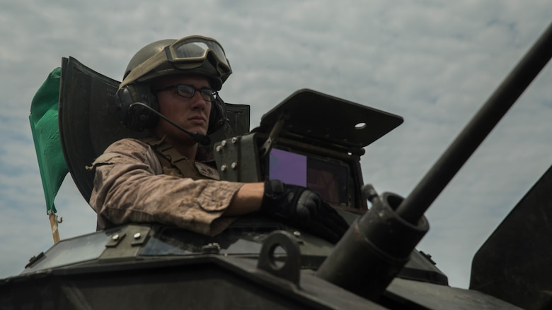 Lance Cpl. Kevin Christ, a crewman with Alpha Company, 2nd Assault Amphibian Battalion, spots targets downrange during a live-fire gunnery range at Marine Corps Base Camp Lejeune, North Carolina, July 27, 2016. With a max possible score of 1,000, Marines must fire through ten separate engagements compiling a score of 700 to pass.