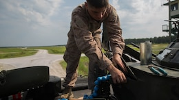An amphibious assault vehicle crewman with Alpha Company, 2nd Assault Amphibian Battalion, loads simulation rounds into a mounted MK-19 40mm grenade launcher during a live-fire gunnery range at Marine Corps Base Camp Lejeune, North Carolina, July 27, 2016. Marines with the battalion spent the day refining their marksmanship skill as individuals and their ability to work as a crew.