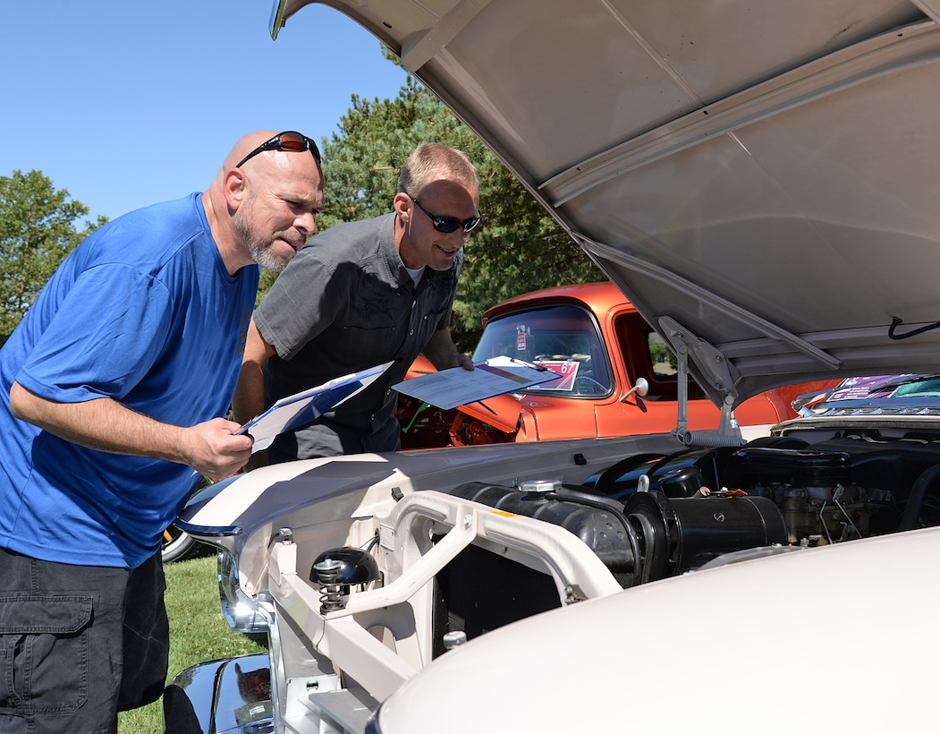 Judges Jason Carrion and John Sowder inspect the original 392 Hemi-engine on a 1957 Chrystal Imperial LeBaron owned by Jerry England. (U.S. Air Force photo by Alex R. Lloyd)