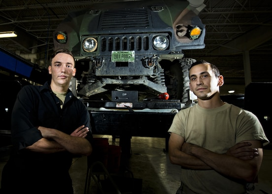 Senior Airman Logan Rivelli (left) and Staff Sgt. Adam Garcia, 5th Logistics Readiness Squadron vehicle maintenance technicians, pose for a portrait in front of a Humvee in the Defender Dome at Minot Air Force Base, N.D., July 28, 2016. Airmen from the 5th LRS vehicle maintenance flight work to ensure that Team Minot stays mobile. (U.S. Air Force photos/Airman 1st Class J.T. Armstrong)