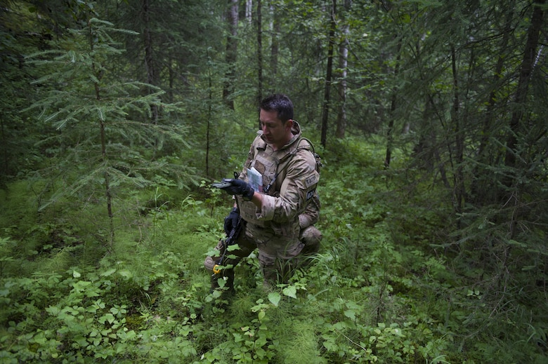 U.S. Air Force Staff Sgt. Kristopher Harpoon, a 5th Air Support Operations Squadron, Joint Base Lewis-McChord, Wash., tactical air control party specialist, checks his compass during the land navigation exercise as part of Cascade Challenge July 19, 2016, at Eielson Air Force Base, Alaska. Competitors were only allowed to use a compass to navigate to their destination. (U.S. Air Force photo by Airman Isaac Johnson)